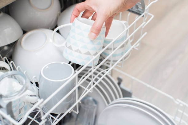 Close Up Of Woman Loading Crockery Into Dishwasher Close Up Of Woman Loading Crockery Into Dishwasher dishwasher stock pictures, royalty-free photos & images