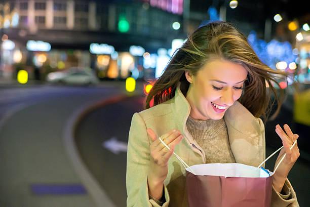 close up of woman  looking at a gift bag - frisuren 2016 frauen stock-fotos und bilder