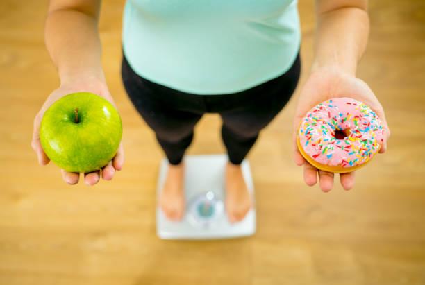 perto da mulher em escala segurando mãos apple e rosca fazendo escolha entre sobremesa saudável alimentos pouco saudáveis durante a medição do peso do corpo no conceito de dieta e tentação de cuidados de saúde de nutrição. - junk food - fotografias e filmes do acervo