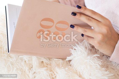 1162245415 istock photo Close Up Of Woman Opening New Year 2020 Diary On bed 1202934684