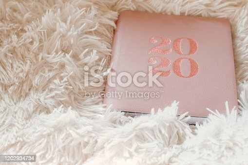 1162245415 istock photo Close Up Of Woman Opening New Year 2020 Diary On bed 1202934734