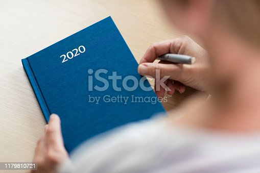 istock Close Up Of Woman Opening New Year 2020 Diary On Table 1179810721