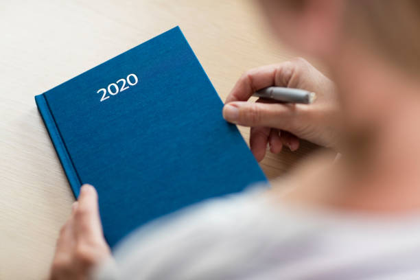 close up of woman opening new year 2020 diary on table - diario foto e immagini stock