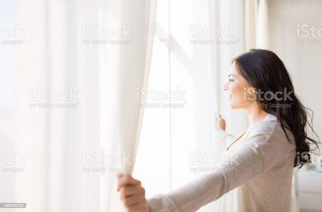 close up of woman opening window curtains royalty-free stock photo