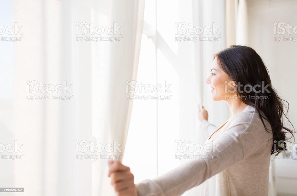 Nahaufnahme von Frau öffnen Fenstervorhänge – Foto