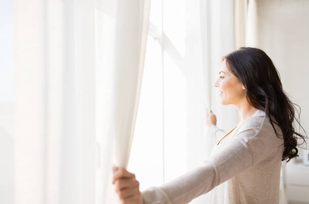 close up of woman opening window curtains stock photo