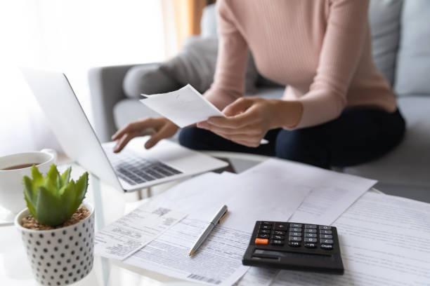 el primer plano de la mujer paga impuestos sobre las facturas en el ordenador portátil - factura fotografías e imágenes de stock