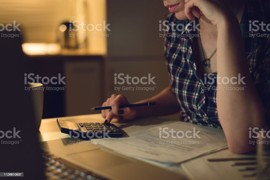 Close up of woman using calculator while going through home finances