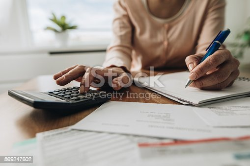 istock Close up of woman planning home budget and using calculator. 869247602