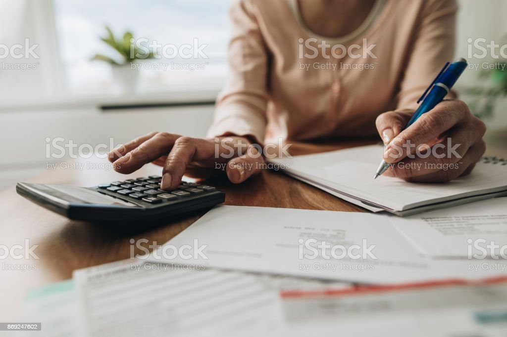 Close up of woman planning home budget and using calculator. stock photo