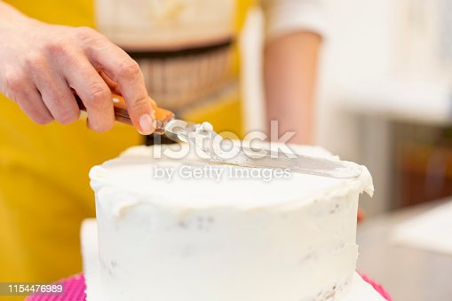 Adult woman in small business workshop decorating a cake and putting icing on top with spatula