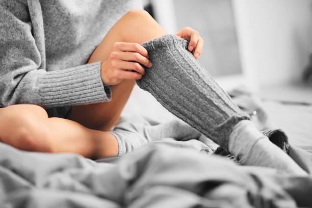 close up of woman putting on the leg warmer - feet hand imagens e fotografias de stock