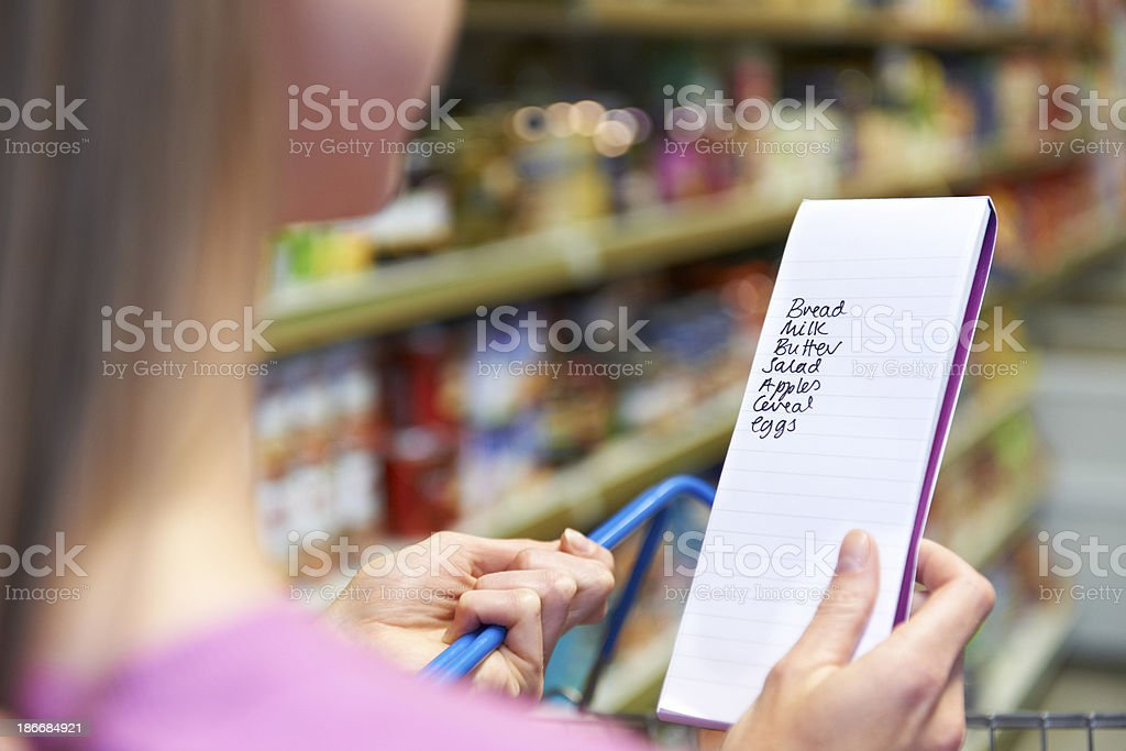 Close Up Of Woman Reading Shopping List In Supermarket royalty-free stock photo