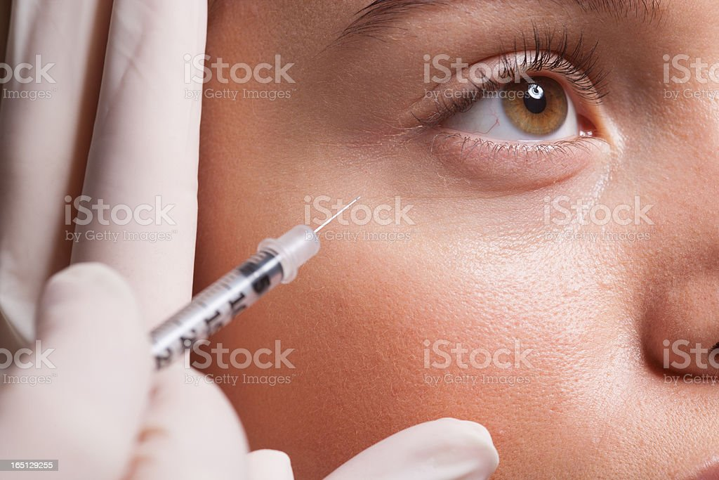 Close up of woman receiving botox injection under eye stock photo