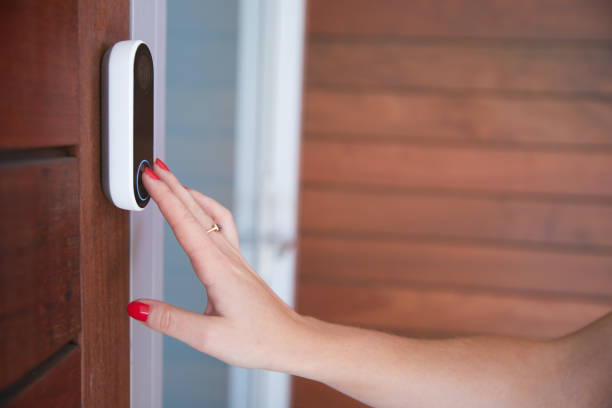 Close Up Of Woman Ringing Front Doorbell Equipped With Security Video Camera stock photo