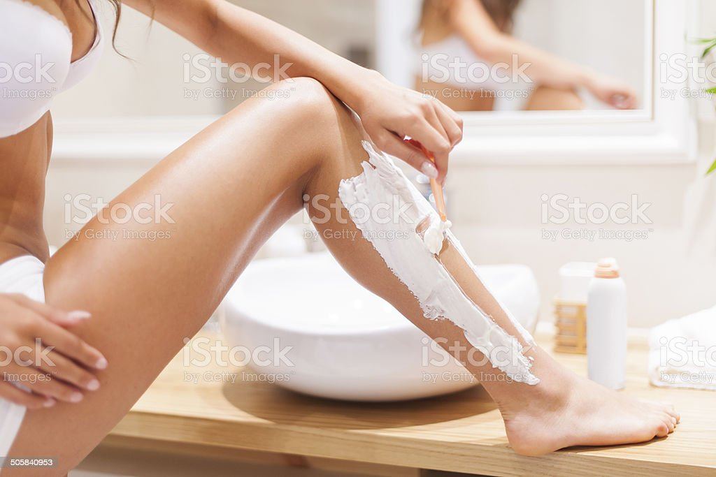 Close up of woman shaving legs in bathroom stock photo