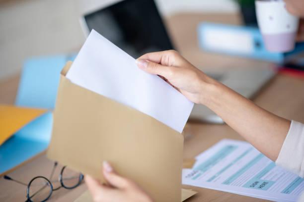 Nahaufnahme der Frau, die Brief aus dem Umschlag nimmt – Foto