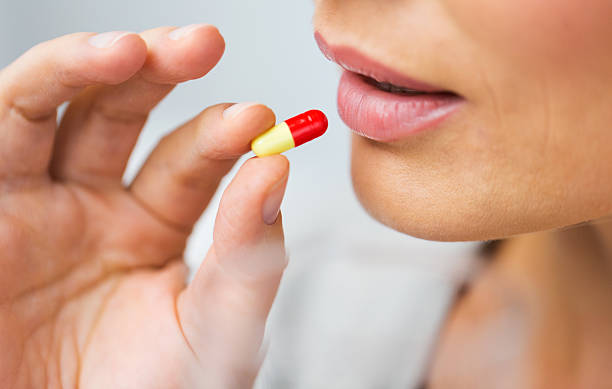 close up of woman taking medicine in pill stock photo