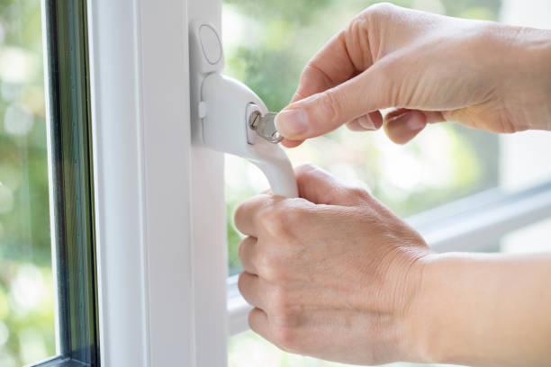 close-up da mulher de girar a chave na fechadura da janela - fechadura - fotografias e filmes do acervo