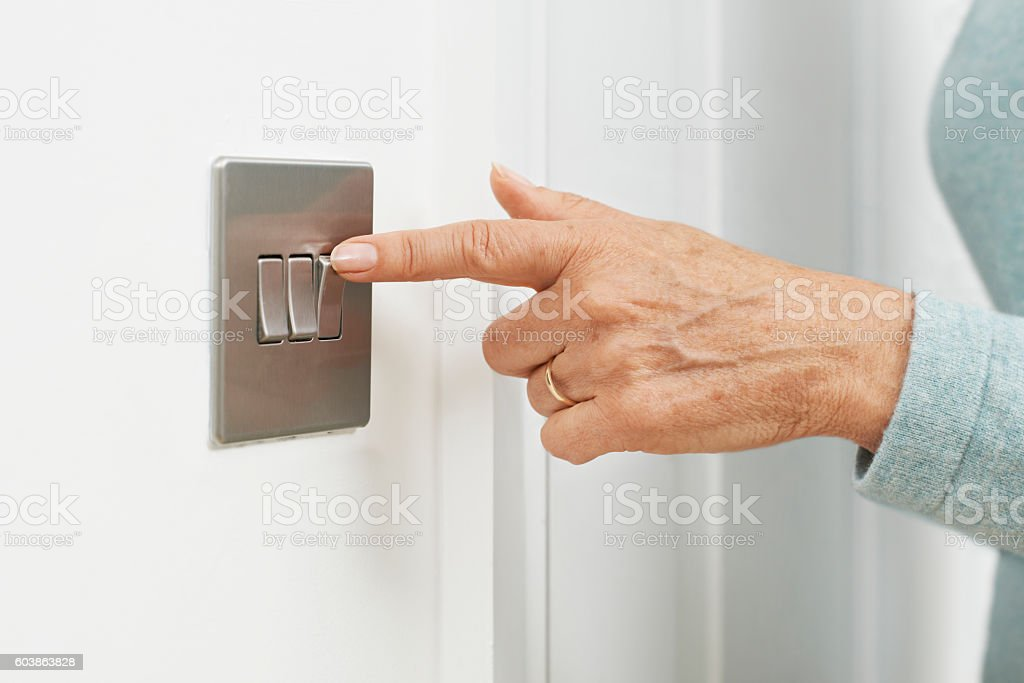 Close Up Of Woman Turning Off Light Switch stock photo
