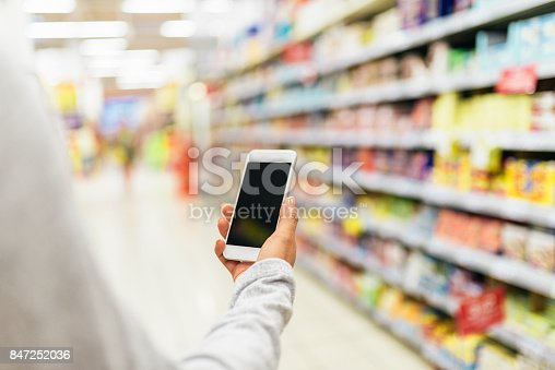istock Close up of woman using her mobile in supermarket. 847252036