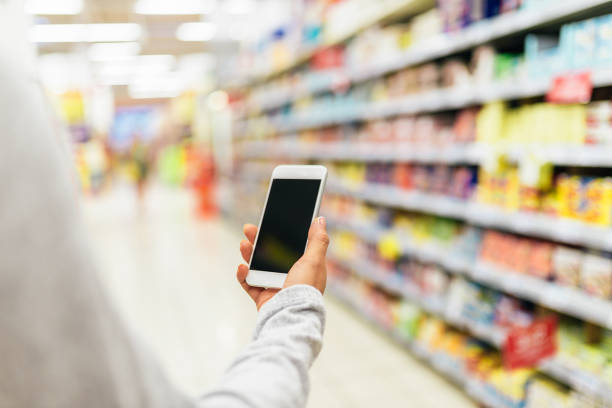 close up of woman using her mobile in supermarket. - app store stock photos and pictures