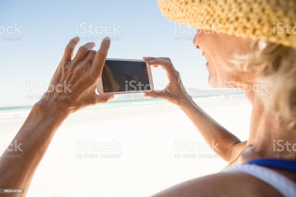 Close up of woman using smart phone while standing against sky royalty-free stock photo