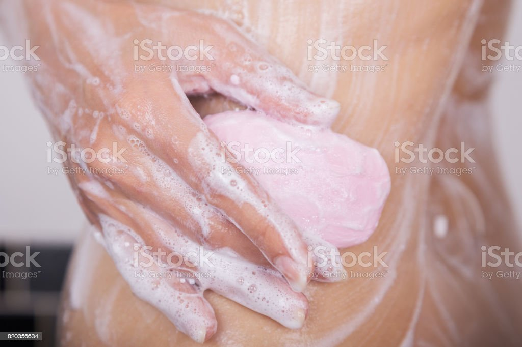close up of woman washing body with soap stock photo