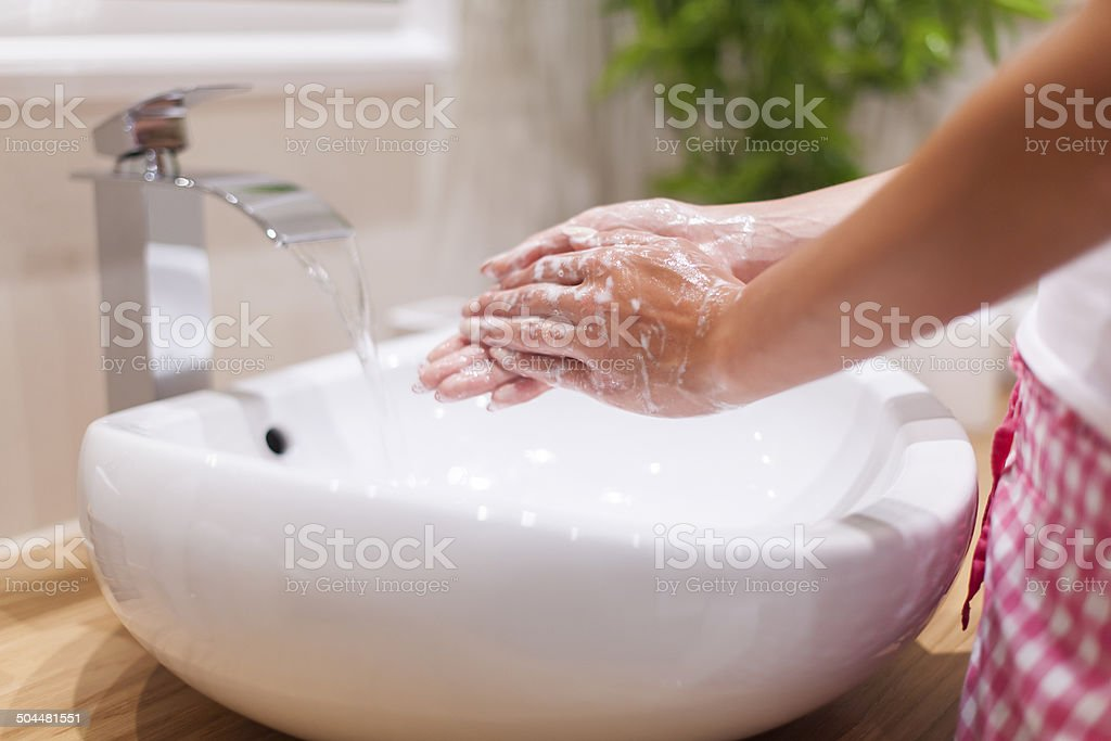 Close up of woman washing hands in bathroom stock photo