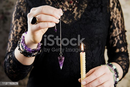 istock Close up of woman wearing black gothic clothing, hand holding and using amethyst crystal pendulum on silver chain fortune telling pendulum in hand. Mystical psychic dark witch reading palm concept. 1137783529