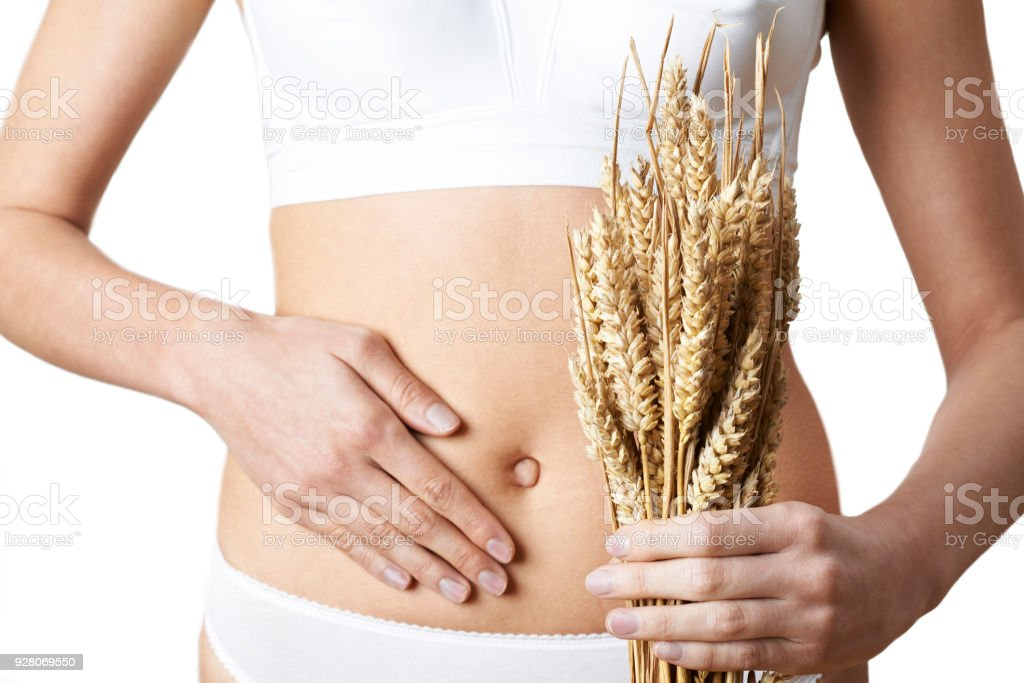 Close Up Of Woman Wearing Underwear Holding Bundle Of Wheat And Touching Stomach stock photo