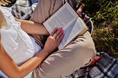 Young woman reading book in nature and sitting on a blanket on hot summer sunset. Girl holding an opened book on legs. Relaxation and enjoying concept. Close up, selective focus