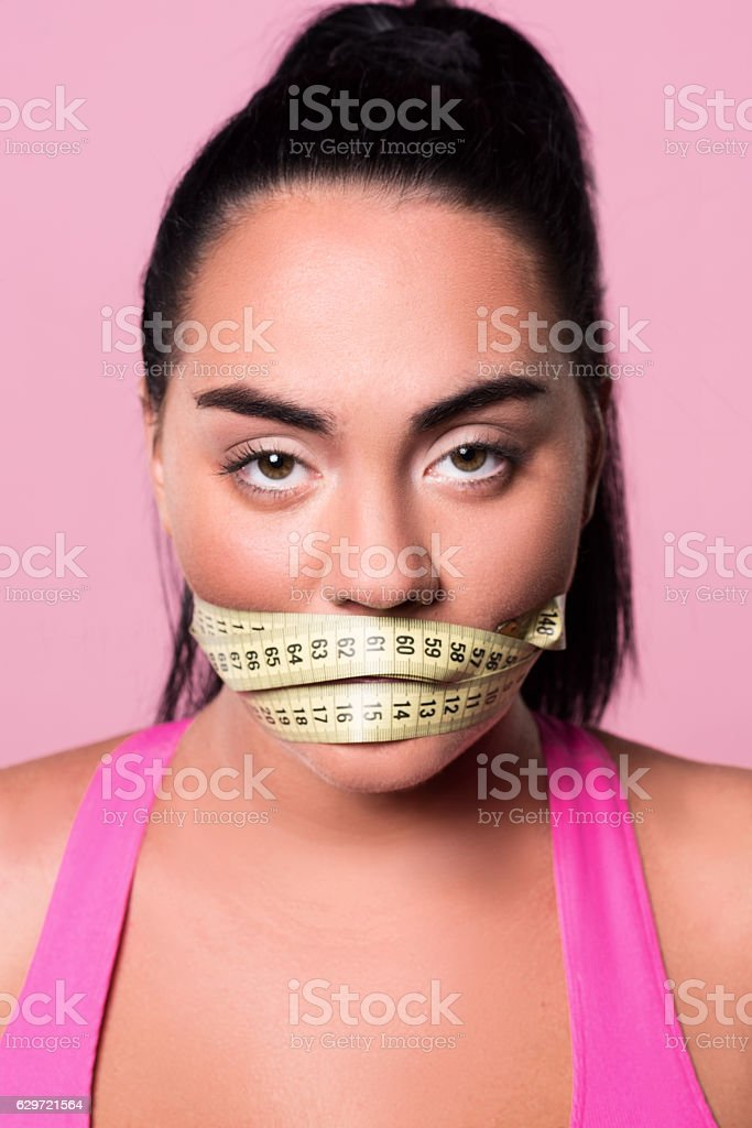 Close up of woman with covered mouth by measuring tape - Photo