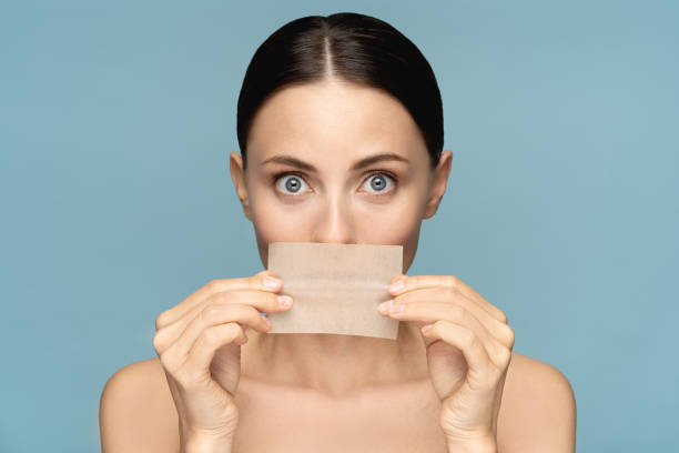 Close up of woman with natural face makeup, holding facial oil blotting paper, hides her lips, looking at camera over blue background. Oil absorbing tissue, shine control, skin care Close up of woman with natural face makeup, holding facial oil blotting paper, hides her lips, looking at camera over blue background. Oil absorbing tissue, shine control, skin care. Beauty product. blotting paper stock pictures, royalty-free photos & images