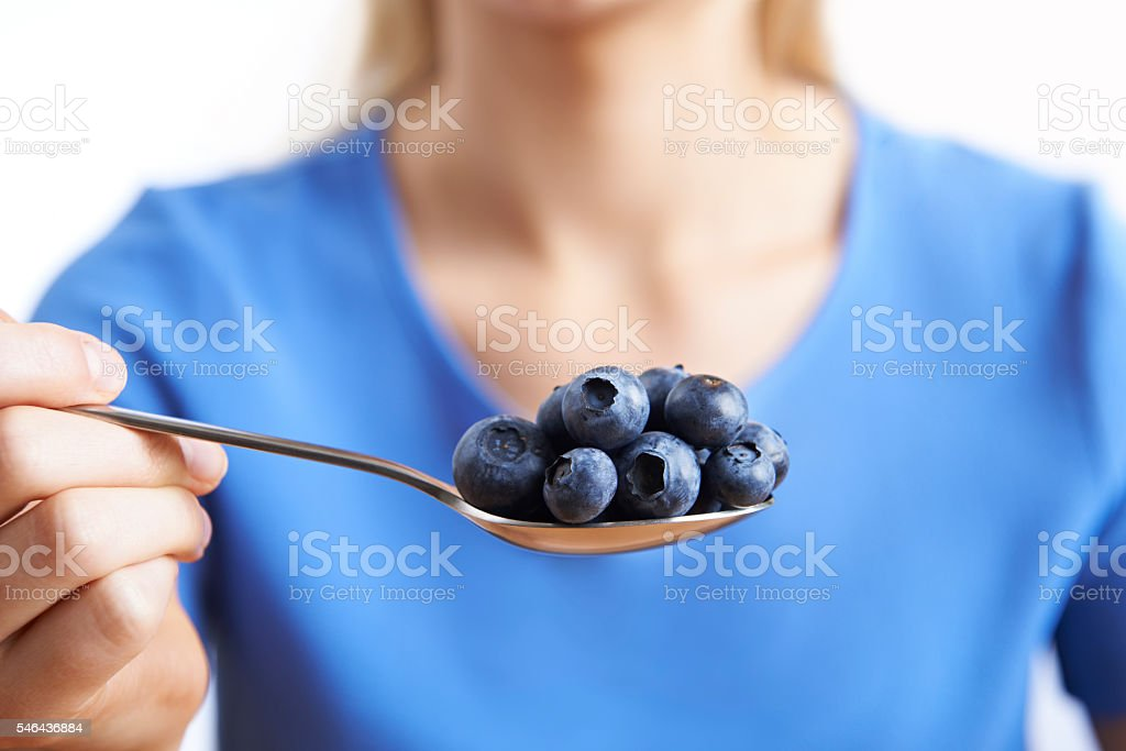 Close Up Of Woman With Spoonful Of Blueberries stock photo