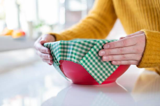 Nahaufnahme der Frau Wrapping Food Bowl In wiederverwendbar engem umweltfreundlichen Bienenwachs Wrap – Foto