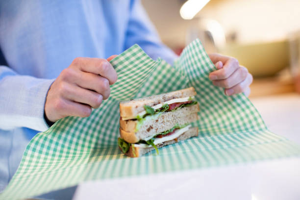 close up of woman wrapping sandwich in reusable environmentally friendly beeswax wrap - avvolto foto e immagini stock