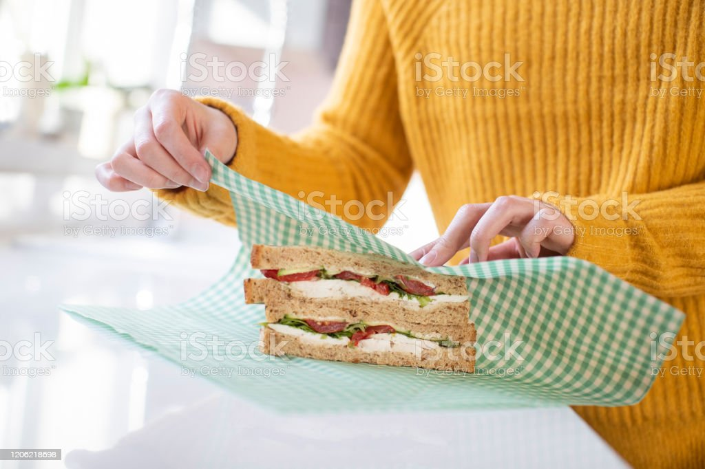 Close Up Of Woman Wrapping Sandwich In Reusable Environmentally Friendly Beeswax Wrap - Foto stock royalty-free di Adulto
