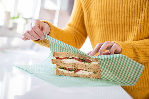 Close Up Of Woman Wrapping Sandwich In Reusable Environmentally Friendly Beeswax Wrap - Fotografie stock e altre immagini di Adulto