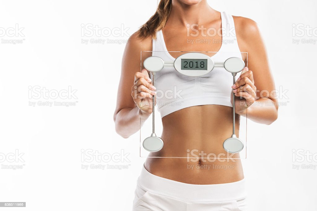 Close up of woman's abdomen, holding a weight scale with a year 2018 written on it - New Year's weigh t loss resolution royalty-free stock photo