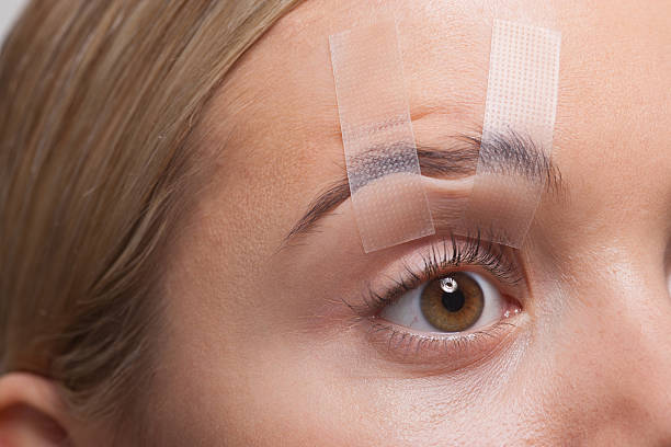 close up of woman's eye taped open - eyelid stock pictures, royalty-free photos & images
