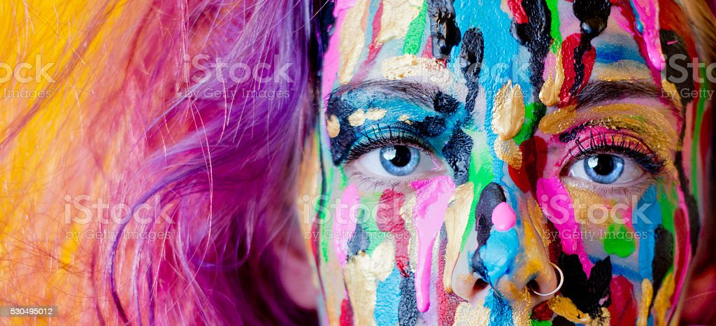 Close Up Of Woman's Face Covered In Dripping Paint stock photo