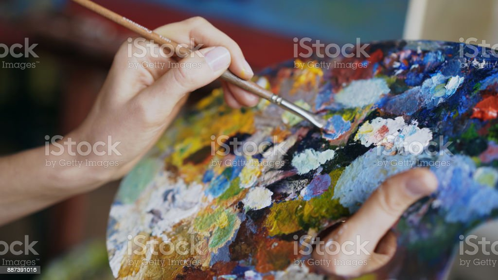 Cerca de las pinturas de mezcla de mano de la mujer con cepillo de paleta en clase de arte - foto de stock