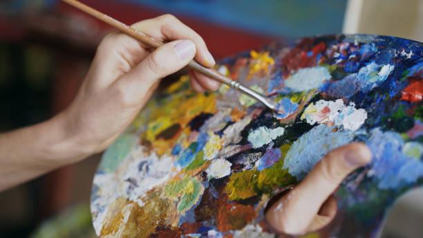 cerca de las pinturas de mezcla de mano de la mujer con cepillo de paleta en clase de arte - clase de arte fotografías e imágenes de stock