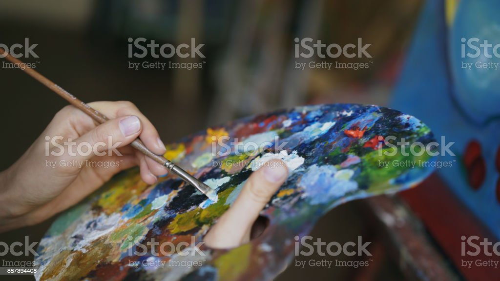Close up of woman's hand mix paints with brush in palette in art-class stock photo