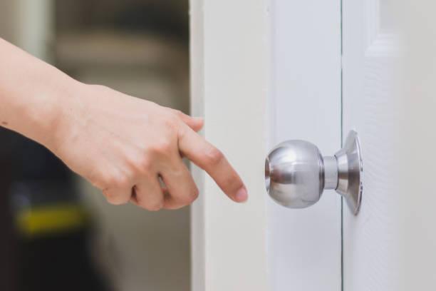 문을 여는 문 손잡이에 도달 하는 여자의 손을 클로즈업합니다 - 문손잡이 뉴스 사진 이미지