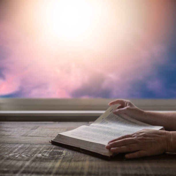 Close up of woman's hand reading Bible, turning page, with dramatic light. Wood table with sun rays coming through window. Christian image stock photo