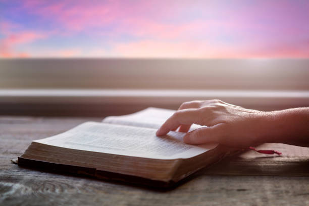 Close up of woman's hand reading Bible, with dramatic light. Wood table with sun rays coming through window. Christian image stock photo