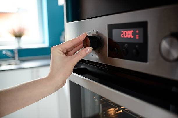 Close up of woman's hand setting temperature control on oven Close up of woman's hand setting temperature control on oven. The display shows the set temperature to 200 degrees Celsius oven stock pictures, royalty-free photos & images