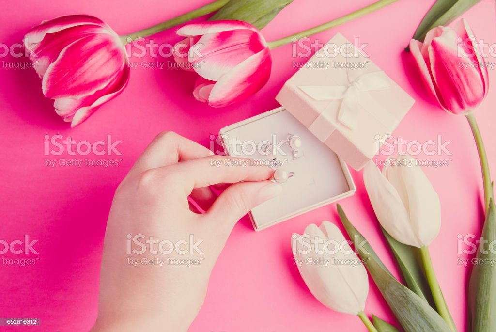 Close up of woman's hand with jewellery and tulips stock photo